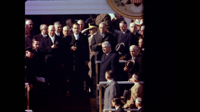 vídeos de stock, filmes e b-roll de / crowd turns to watch as president dwight eisenhower vice president richard nixon and others descend the steps of the capitol building / the band... - tomada de posse