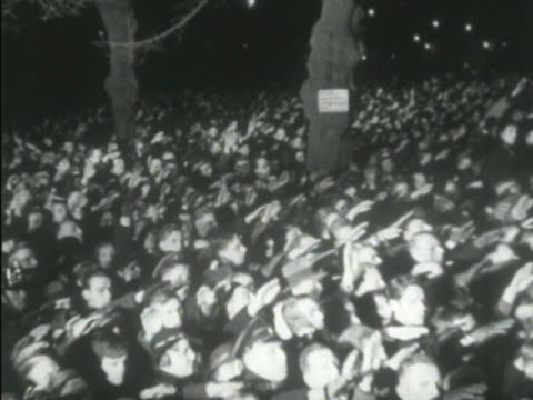 crowd w/ arms outstretched upward nazi salute toward hermann goering hitler standing on building balcony angled ws lighted crowd saluting right ha... - 1938 stock-videos und b-roll-filmmaterial