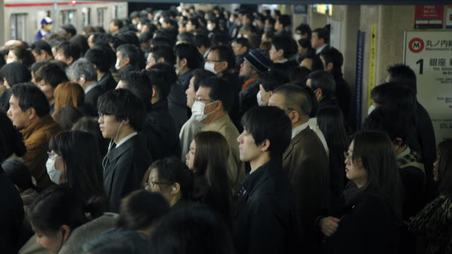 crowd waits for subway at rush hour - tokyo, japan - schienenverkehr stock-videos und b-roll-filmmaterial