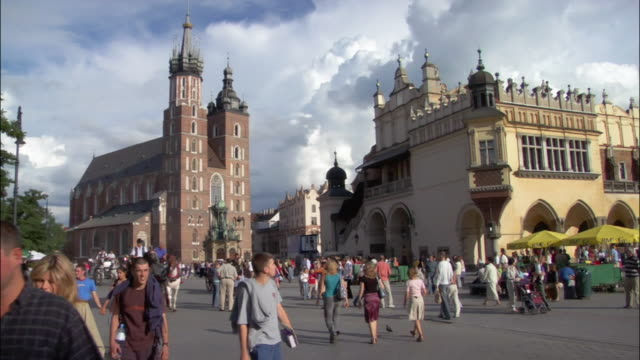 crowd walking and biking in front of st. mary's basilica and cloth hall in plaza of rynek glowny / zoom in as tourists riding in horsedrawn carriages pass by camera / old town, krakow, poland - horsedrawn stock videos & royalty-free footage
