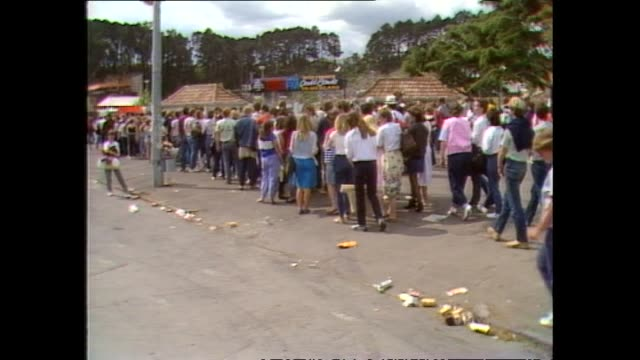 Crowd walking into stadium grounds prior to 1983 David Bowie concert at Western Springs Stadium in Auckland bags being checked by security and...