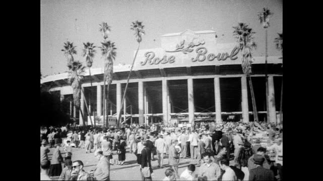 / crowd walking into the rose bowl stadium / newsmen with cameras above the giant crowd of thousands / game begins / individual players mentioned are... - anno 1954 video stock e b–roll