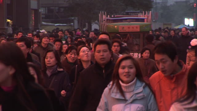 ws crowd walking through nanjing road at dusk/ shanghai, china - population explosion stock videos and b-roll footage