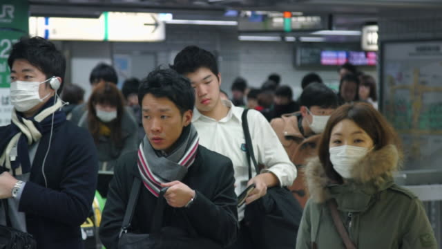 crowd walks to subway at rush hour - tokyo, japan - mask stock videos & royalty-free footage