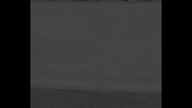 vidéos et rushes de crowd watches action at masters tournament / ben hogan stands in sand trap and hits ball out onto grass / hogan putts ball into hole then walks and... - ball trap