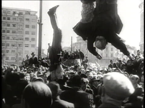 a crowd watches as a dead body is hoisted up next to the body of benito mussolini and his mistress - benito mussolini bildbanksvideor och videomaterial från bakom kulisserna