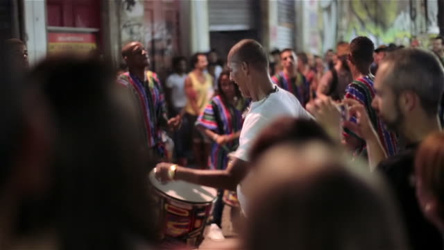 Crowd watches as happy man dances to Brazilian samba music on the streets of Rio