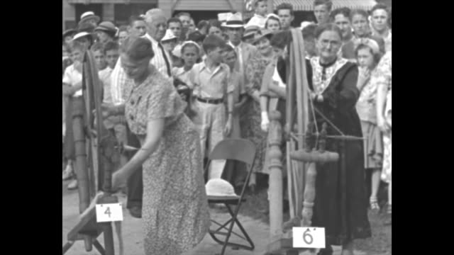ms crowd watches as two grandmothers work spinning wheels / cu one grandmother's face and shoulders as she spins wheel during celebration of mercer... - pearl jewellery stock videos & royalty-free footage