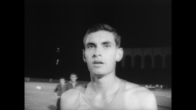 crowd watches in the los angeles coliseum as jim ryun and others compete in the compton mile race / ryun passes rival jim grelle / ryun sprints last... - 第4クオーター点の映像素材/bロール
