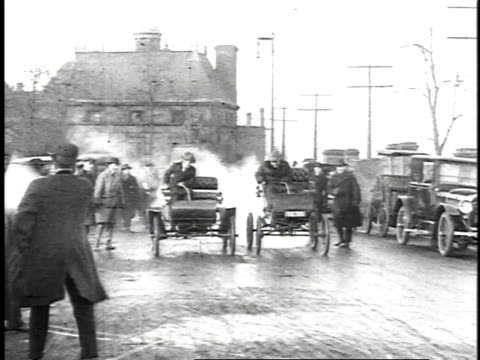 1923 ws crowd watching a car race between two men driving very early cars / united states  - 1923 stock-videos und b-roll-filmmaterial