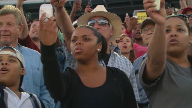 vídeos de stock e filmes b-roll de la ms pan crowd watching anxiously in bleachers, then take photos with cell phones in unison / homestead, fl, usa - pista de desporto