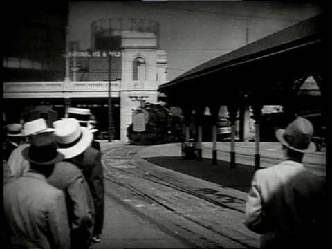 "vídeos de stock, filmes e b-roll de 1933 ws crowd watching approaching train bearing banner reading ""honeywell rubber company convention special"" / atlantic city, new jersey, united states - 1933"