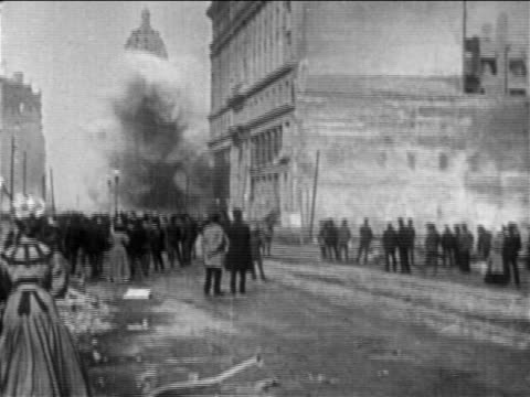 view crowd watching building collapsing after san francisco earthquake / documentary - erdbeben stock-videos und b-roll-filmmaterial