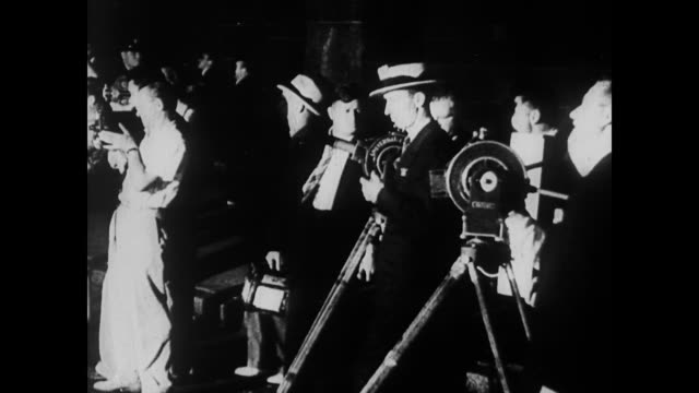 vidéos et rushes de / crowd watching man on building / newsreel camermen / man falls catches himself on awning then hits the ground / body covered by police man jumps... - 1935