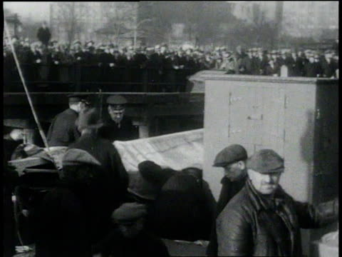vidéos et rushes de crowd watching on shore / bottles of golden wedding whiskey - 1931