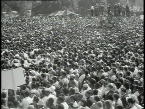vídeos de stock e filmes b-roll de crowd watching performance at rally / crowd walking towards washington monument - 1963