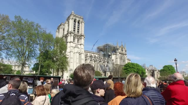 vidéos et rushes de crowd watching the cathedral. the cathedral notre-dame without roof with scaffolding, south side of the cathedral.paris: view of the cathedral... - plan en travelling