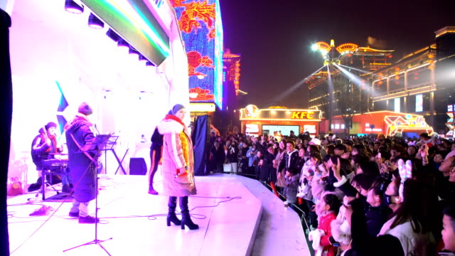 crowd watching the performance at scenic spot for celebrate chinese spring festival / xi'an, shaanxi, china - 中国文化点の映像素材/bロール