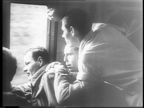crowd waves from platform as train pulls away / interior of train as soldiers look out the window / soldiers reading newspapers on train / close-up... - ホームカミング点の映像素材/bロール