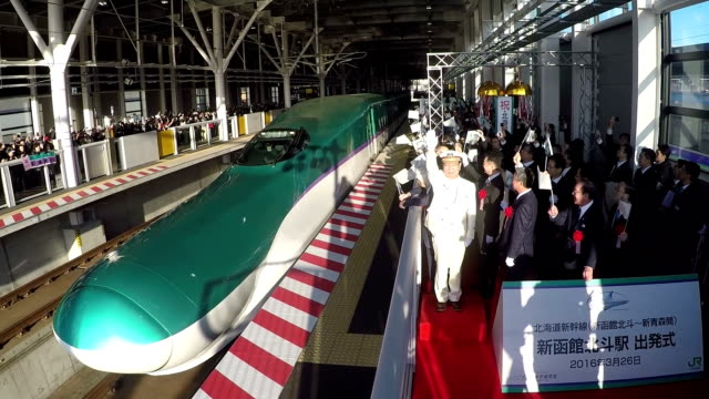 a crowd waving flags and snapping photos in hokuto hokkaido saw off the new hokkaido shinkansen as it departed from shinhakodatehokuto station on its... - kyushu shinkansen stock videos & royalty-free footage