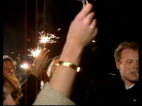 crowd waving sparklers in celebration of opening of berlin wall 09 nov 89 - 1989 stock-videos und b-roll-filmmaterial