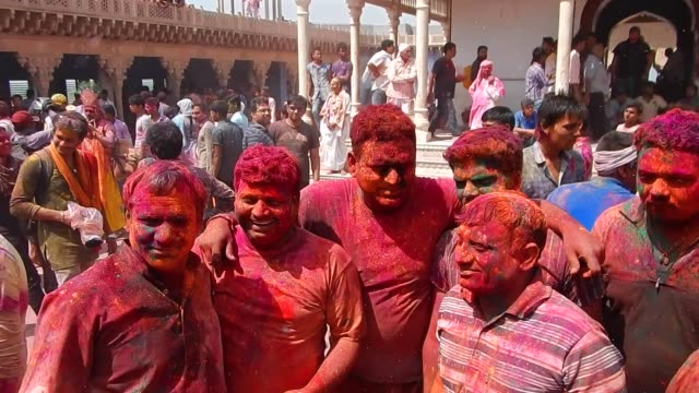 vídeos y material grabado en eventos de stock de crowd with brightly coloured faces / religious festivities and celebrations inside the temple complex in nandgaon mathura the village of lord krishna... - krishna
