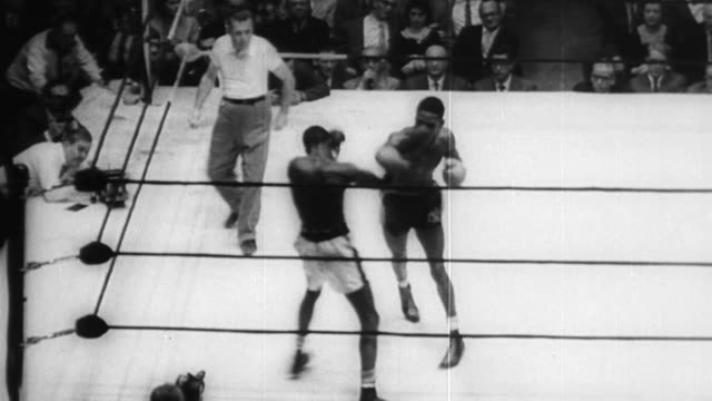 crowded arena with boxing ring at center / two african american boxers fight william pickett and willy moran / crowd cheers vigorously / fighting... - boxing heavyweight stock videos & royalty-free footage