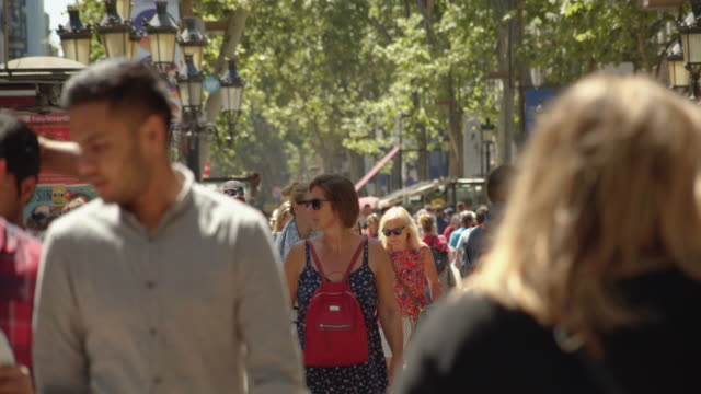 crowded barcelona ramblas. famous street establishing shot filmed slow motion with telephoto lens with defocused people - telephoto lens stock videos and b-roll footage