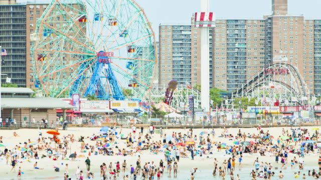 crowded beach and funfair at coney island, new york city, new york, usa - coney island stock-videos und b-roll-filmmaterial