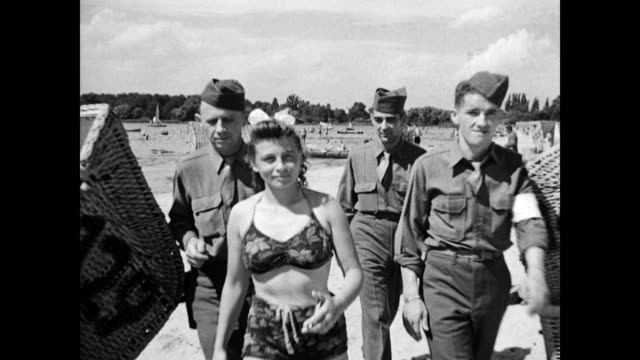 vidéos et rushes de ls crowded beach at wannsee / soldiers looking down on the beach / us soldiers mingling with german girls on the beach / soldiers sunbathing / army... - 1945