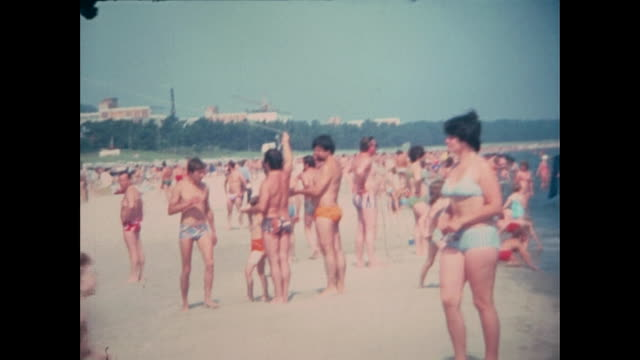 crowded beach, tourists bathing and relaxing at the beach in front of the famous kurhotel / grand hotel travel charme at the island rügen, kids... - ostsee stock-videos und b-roll-filmmaterial