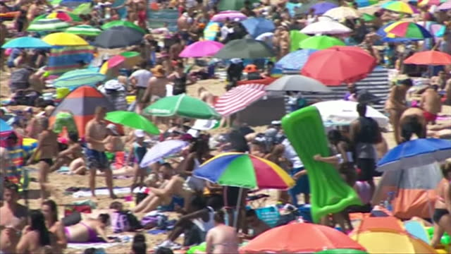 crowded bournemouth beach in the heatwave during coronavirus lockdown crowds make it hard for social distancing to be observed - bournemouth stock-videos und b-roll-filmmaterial