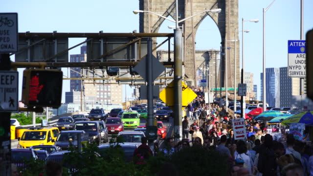 Crowded Brooklyn Bridge walkway at the right, and heavy traffic at the left of the Brooklyn Bridge New York. Image was captured from Manhattan ward.