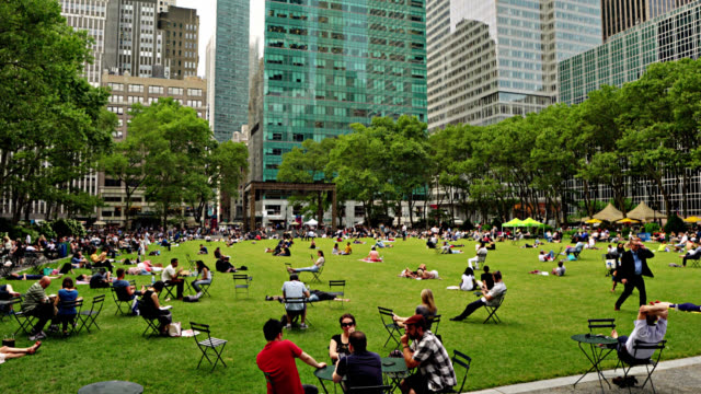 crowded bryant park and view of financial and corporate buildings. nature and cityscape. relaxation and business. concept. - bryant park stock videos & royalty-free footage