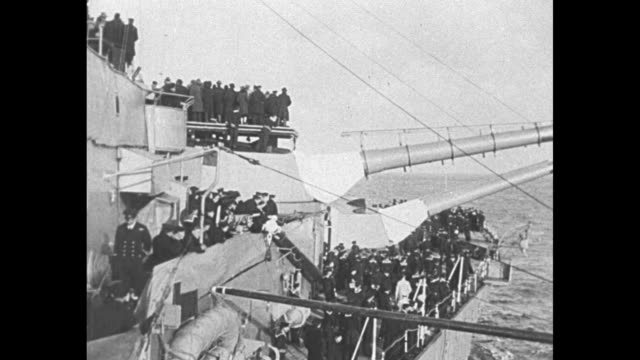crowded deck of the hms revenge, with the representatives of the british commonwealth nations posing under a large, lowering artillery gun / high... - british military stock-videos und b-roll-filmmaterial