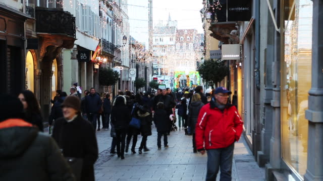 a crowded european street with tourists, pedestrians, and holiday decorations - besichtigung stock-videos und b-roll-filmmaterial