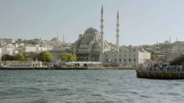 ws crowded ferries floating through a harbor in the bosphorus strait with the yeni camii mosque in the distance / istanbul, turkey - yeni cami mosque stock videos and b-roll footage