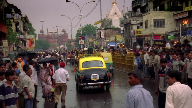 pan crowded india street in rain - risciò video stock e b–roll