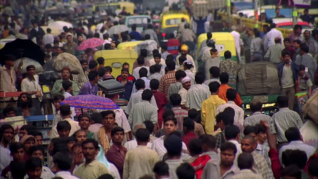 vidéos et rushes de pan, ms crowded india street in rain - inde