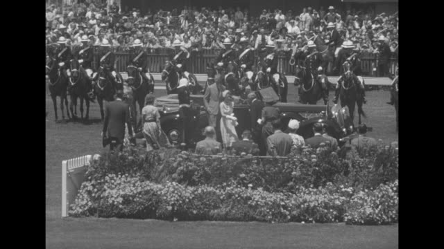 vídeos de stock e filmes b-roll de crowded infield as elizabeth in open car drives into view escorted by numerous horsemen / she exits the car and is greeted / she and racetrack... - presidente de empresa