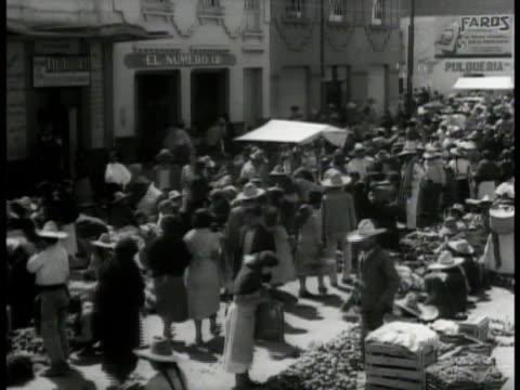 vídeos y material grabado en eventos de stock de crowded mexican food market vs mexicans shopping crates of fruits vegetables - 1935
