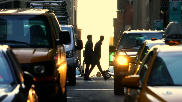 Crowded Midtown Manhattan traffic during the evening commute time on Mar. 29 7017. Commuters cross the street among the congestion traffic. The silhouettes of commuters appear in the sunset glow sky.