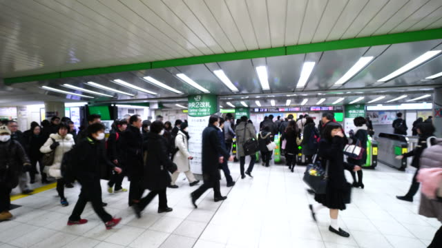 crowded morning commute scene at jr ikebukuro station.commuters are migrating the underground passage and go to the automatic ticket gates. - 自動改札機点の映像素材/bロール