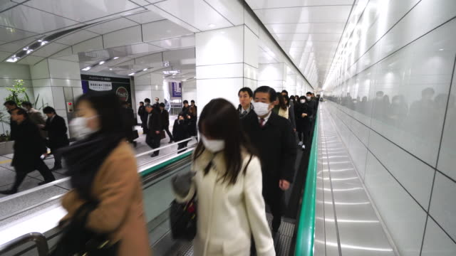 TL Crowded morning commute scene at JR Shinjuku Station underground passage.Commuters are walking on the Moving walkway of underground passage to Shinjuku Subcenter Business District.