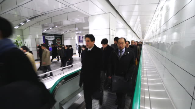 Crowded morning commute scene at JR Shinjuku Station underground passage.Commuters are walking on the Moving walkway of underground passage to Shinjuku Subcenter Business District.