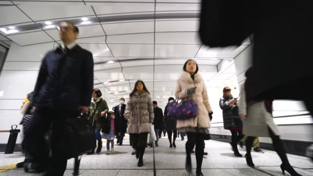 crowded morning commute scene at jr shinjuku station underground passage.commuters going through the underground passage to shinjuku subcenter business district. - 保護マスク点の映像素材/bロール