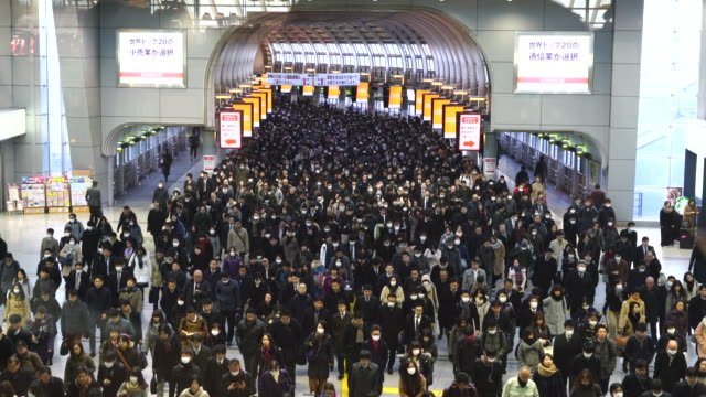vídeos de stock e filmes b-roll de crowded morning commute scene at konan exit jr shinagawa station at shinagawa tokyo japan – january. 26 2018. commuters are going through the rainbow road passageway to go to the office in shinagawa business district. - distrito financeiro