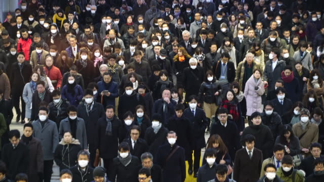 crowded morning commute scene at konan exit shinagawa station at shinagawa tokyo japan – january. 26 2018. commuters are going through the rainbow road passageway to go to the office in shinagawa business district. - pollution mask stock videos & royalty-free footage