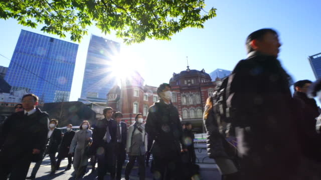 crowded morning commute scene at marunouchi business district.commuters go to marunouchi business district from tokyo station. - pollution mask stock videos & royalty-free footage