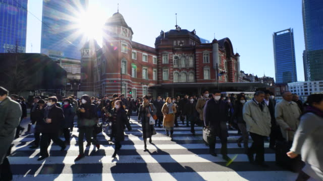 crowded morning commute scene at marunouchi business district.commuters go to marunouchi business district from tokyo station. - pedestrian crossing stock videos & royalty-free footage
